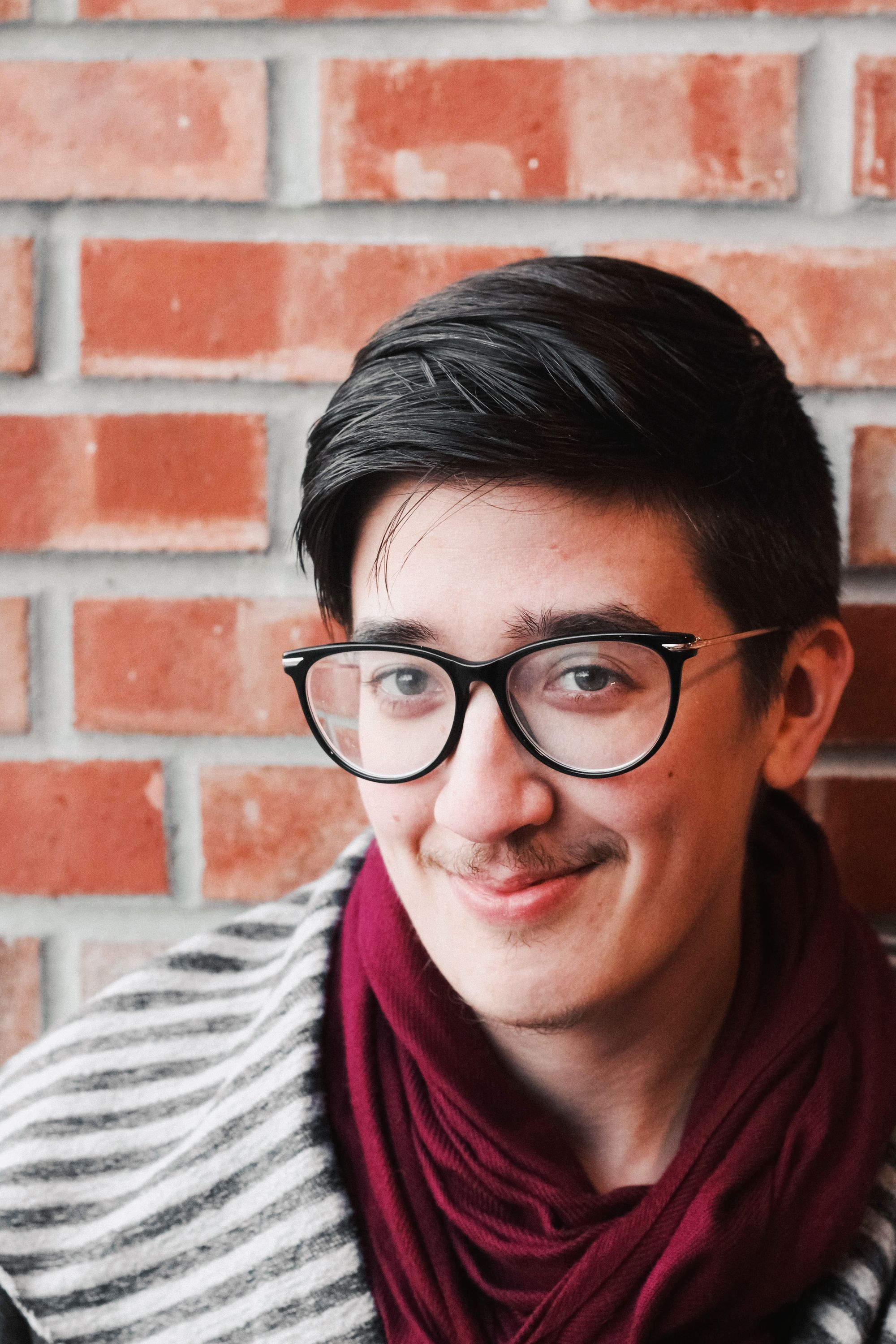 Nino Cipri is a winsome person with short dark hair, glasses, and a mischievous smile. They have a trim moustache and beard. In this image, they're standing next to a brick wall, wearing a black-and-grey striped top with a deep red scarf.