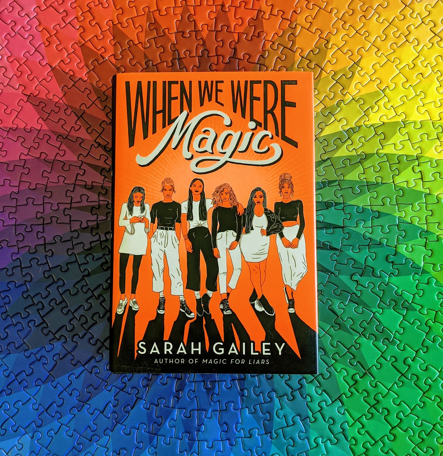 When We Were Magic has a bright orange cover featuring six femmes in black-and-white clothes looking like they don't give a shit about anyone else but each other. Here, the book is shown resting on a puzzle that is a rainbow spirograph. That puzzle took me a super long time to finish. I'm real proud of it.